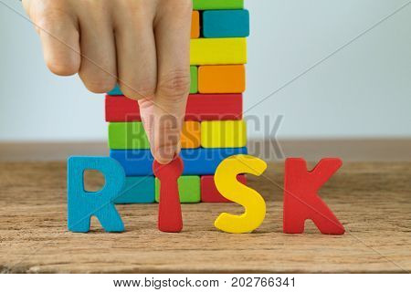 risk concept with hand holding colorful wooden alphabets RISK and wooden blocks tower in the background.