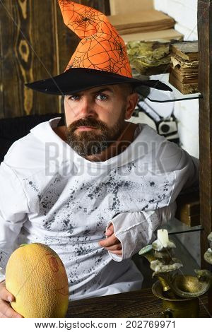 Man In Orange Hat With Concerned Face Holds Painted Pumpkin