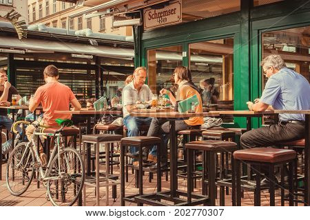 VIENNA, AUSTRIA - JUN 6, 2013: Couple talking and other people drinking in in outdoor city bar with tall tables on June 6, 2013. Vienna city has population near 1.8 million
