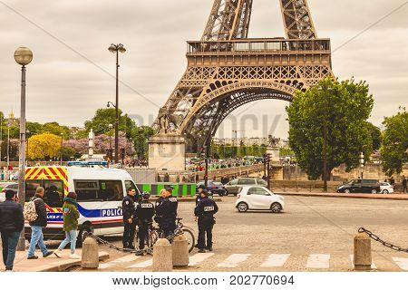 Police Truck Is Parked In The Street In Front Of The Eiffel Tower