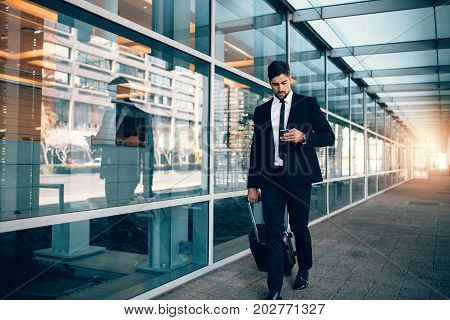 Businessman Walking With Luggage And Using Mobile Phone At Airpo