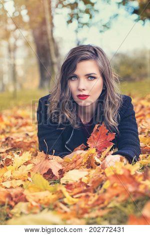 Autumn Woman Lying on Fall Leaves in Beautifu Autumn Park Outdoors