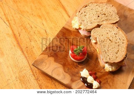 Sandwiches on a wooden plate served with tomato and sauces