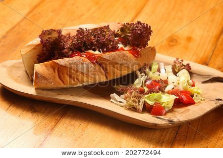 Fresh and delicious baguette sandwich on the wooden board