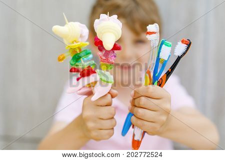 Happy little kid boy holding marshmallow skewer in one hand and toothbrushes in another. Child with different unhelthy colorful sweets. Healthy food and teeth concept. Selective focus on hands