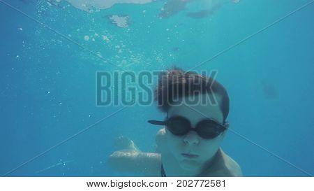 Boy teenager swims under water in the pool. Happy childhood underwater rest bathe boy