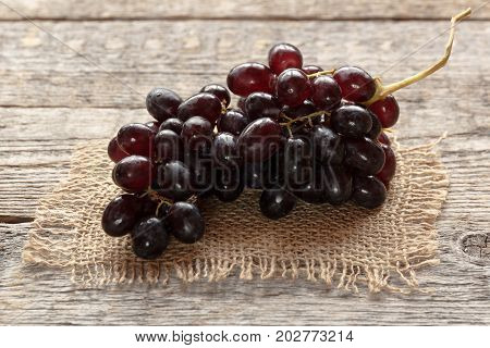 Ripe dark grapes with leaves on wooden background. Selectiva focus. Copy space