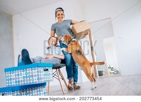 Mother with little son and beagle dog in new apartment after renovation