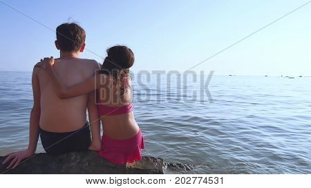 Boy and girl on sea. A boy and a girl are sitting on the rocks on the sea view from the back of a romance happy childhood and dreams