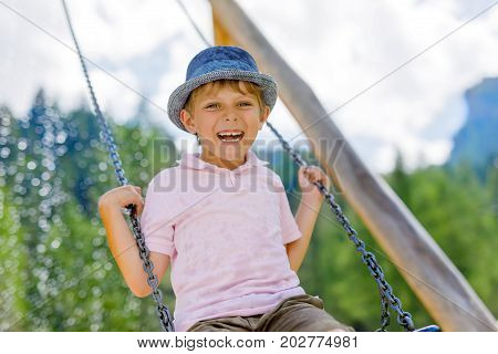 Funny kid boy having fun with chain swing on outdoor playground. child swinging on warm sunny summer day. Active leisure with kids. Happy crying boy
