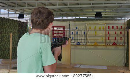 Boy teen shoots in dash from the machine gun. Airguns gun