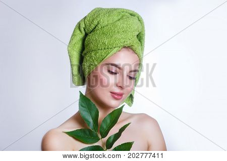 woman with a green towel on her head .Beautiful woman face portrait with green leaf concept for skin care or organic cosmetics