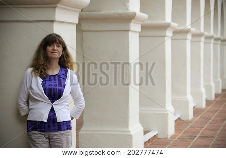 SAN DIEGO, CALIFORNIA, JUNE 10. Presidio Park on June 10, 2017, in San Diego, California. A Smiling Woman Stands Amid the Columns of Spanish Revival Style Architecture in Presidio Park San Diego.
