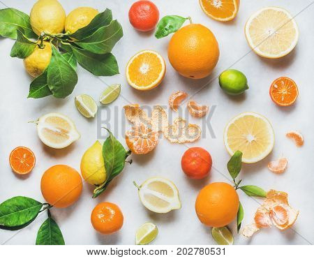 Variety of fresh citrus fruits for making juice or smoothie over light grey marble table background, top view, horizontal composition. Healthy eating, vitamin, detox, diet food, clean eating concept