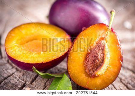 Plum. Healthy juicy ripe organic plums fruit close-up, on wooden table. Prune. Sweet fruits dessert.