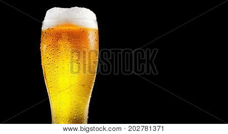 Beer. Cold Craft light Beer in a glass with water drops. Pint of Beer close up isolated on black color background. Border design