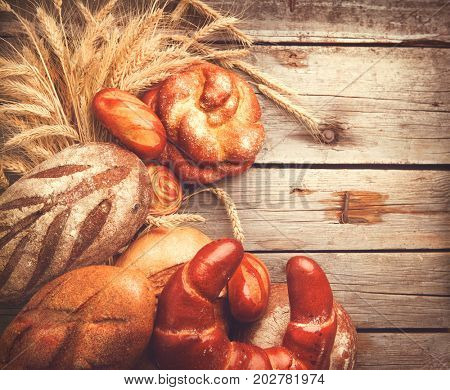 Bakery Bread border on a Wooden Table. Various Bread and Sheaf of Wheat Ears Still-life. Copy space for your text.