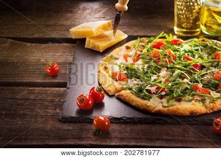 Pizza Caprese with arugula, cheese, yoghurt and cherry tomatoes close up. Homemade delicious italian vegetarian pizza on wooden table, food.