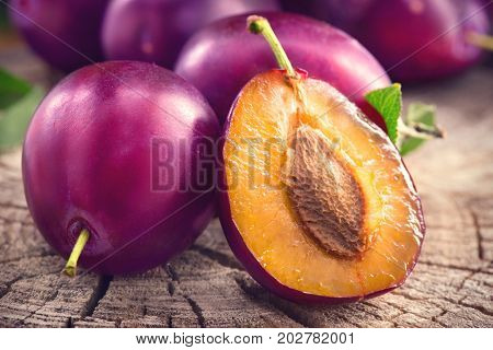 Plum. Healthy juicy ripe organic plums fruit close-up, on wooden table. Prune. Sweet fruit dessert.