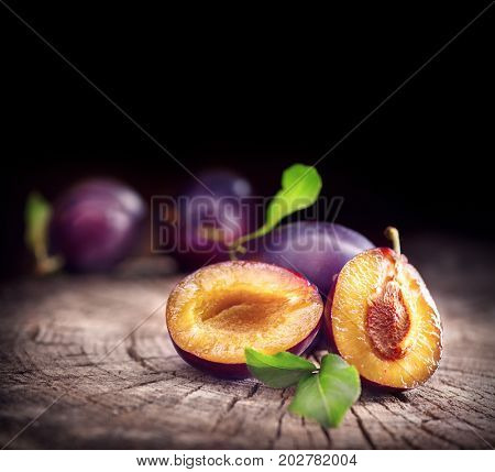 Plum. Healthy juicy ripe organic plums fruit close-up, on wooden table. Sweet dessert over black background and space for your text