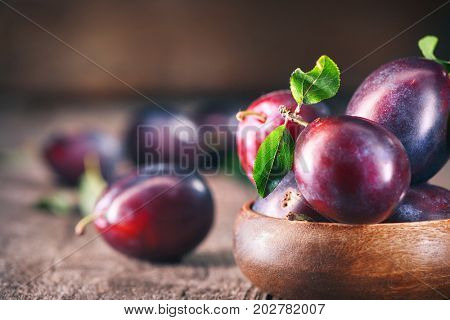 Plum. Healthy juicy ripe organic plums fruit close-up, on wooden table. Prune. Sweet dessert.