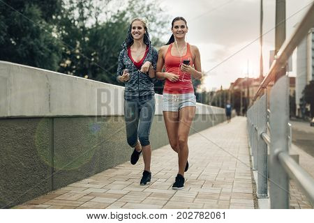 Active female joggers running outdoors and listening to music