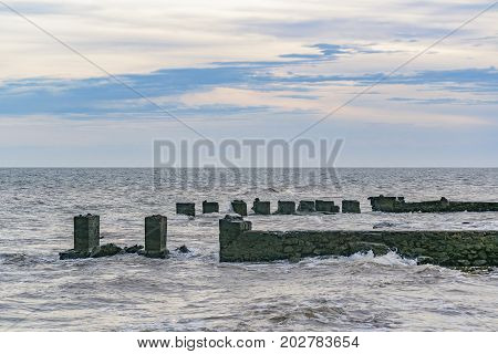 Broken Breakwater At River