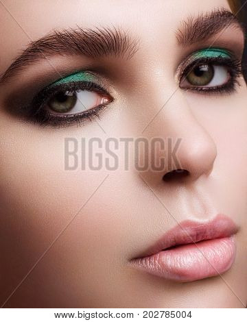Largely a portrait of the beautiful girl with fashionable cosmetics on a face. Smoky eyes big eyebrows and chubby natural lips. Cosmetology beauty shop cosmetics injections