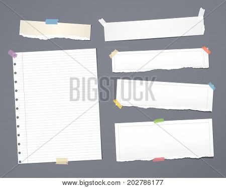 White striped note paper, copybook, notebook sheet stuck with adhesive tape on dark gray background