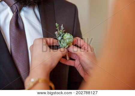 The bride wears a boutonniere on the jacket to the groom