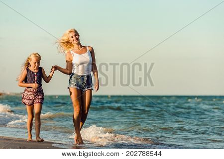 Happy family during summer vacation on against the sea, ocean on a summer day. Mother and daughter on the beach