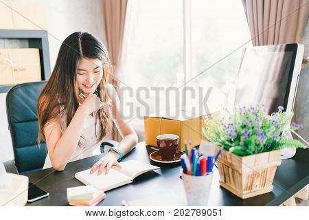 Young and beautiful Asian small business owner work at home office organizing purchase orders. Online marketing packaging delivery startup SME e-commerce or businesswoman entrepreneur concept