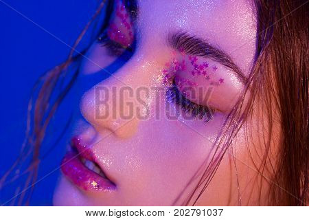 Macro shot of the fashionable photo in neon flowers of light. The shining skin is covered with spangles and stars. Wet hair and the sensual woman for cosmetology Spa and thematic parties
