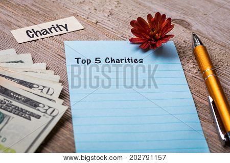 Top 5 Charities concept on notebook and wooden board