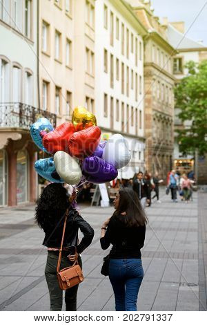 PARIS FRANCE - JUL 12 2017: Two young beautiful girls walking on the street with a helium balloon smiling cheerful being happy