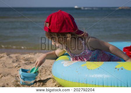 Summer vacations - little girl playing on sea sand beach and plays with sand