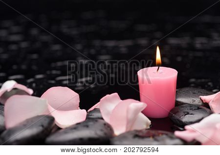 Still life with pink rose ,petals with white candle and therapy stones