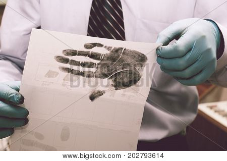The investigator takes fingerprints from the suspect in the crime. Investigation is a crime.