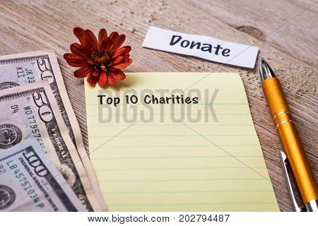 Top 1 Charities and Donate concept on notebook and wooden board with money