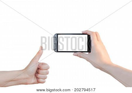 Woman holds in front of herself mobile phone with blank screen and takes photos some event and the approving gesture (thumbs up) shows other hand isolated on white background.