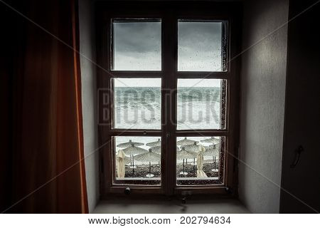 Vintage window with dramatic sea view with big stormy waves and dramatic overcast sky during rain and storm weather in fall season on sea coast
