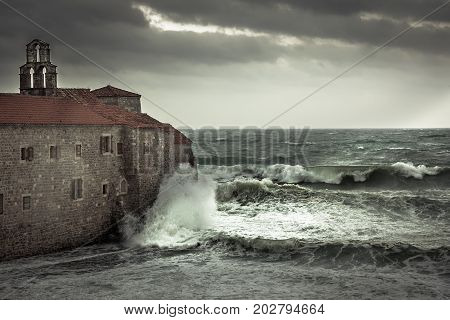 Dramatic landscape with ancient castle on sea shore during storm with big stormy waves and dramatic sky with rain in fall season on sea coast