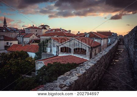 Ancient European city skyline with orange tile roofs and dramatic sky during sunset in antique architecture in old European town Budva in Montenegro