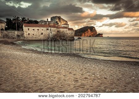 European tourist resort sea fort Budva with medieval architecture at sunset beach with dramatic sky in Europe country Montenegro of Balkan peninsula