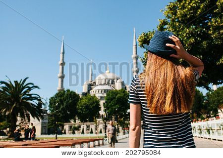 A young girl traveler in a hat from the back in Sultanahmet Square next to the famous mosque called the Blue Mosque in Istanbul, Turkey. Travel, tourism.