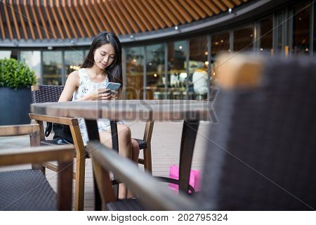 Woman sending sms on cellphone in coffee shop