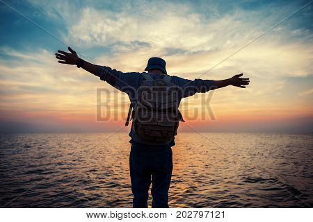 Traveler With Backpack And Outspread Hands Near Sea At Sunset
