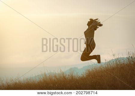 Happy woman enjoying the beautiful nature celebrating freedom and rising her arms while jumping toward the setting sun. Lifestyle and freedom concept.