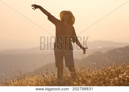 Happy woman enjoying the beautiful nature celebrating freedom and rising her arms while posing toward the setting sun. Lifestyle and happiness concept.