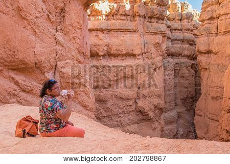 Asian woman drinking water during a break on the Navajo trail, Bryce Canyon, Utah, United States